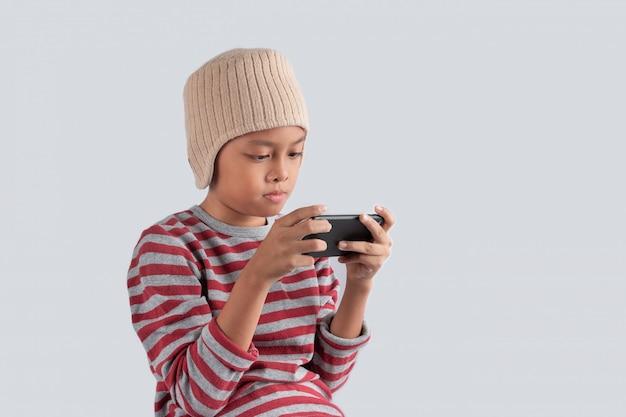 Weinig aziatische jongen in wollen hoed die slimme telefoon op witte achtergrond met behulp van