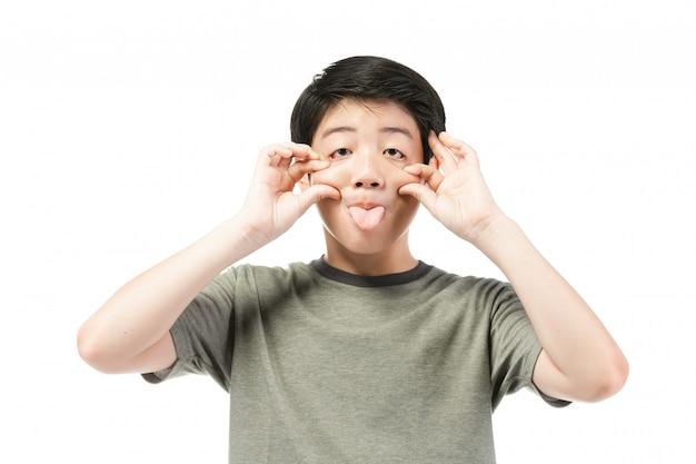 Weinig aziatische jongen met zwart haar in grappig acteren die aan het amuseren proberen.