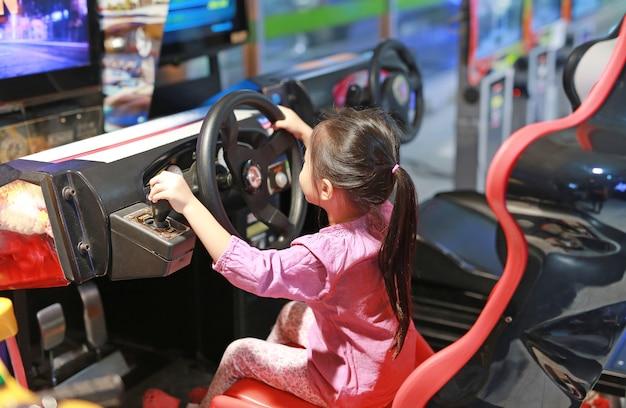 Weinig aziatische jongen spelen arcade racewagen.