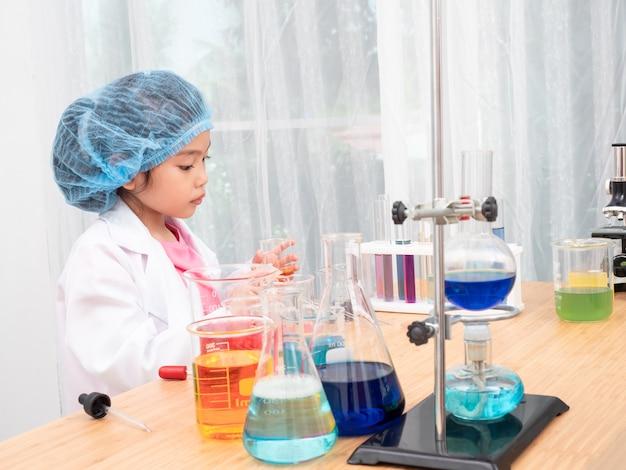 Weinig aziatische leuke meisjesrol die een wetenschapper in wetenschapslaboratorium spelen met apparatuur en chemische producten.