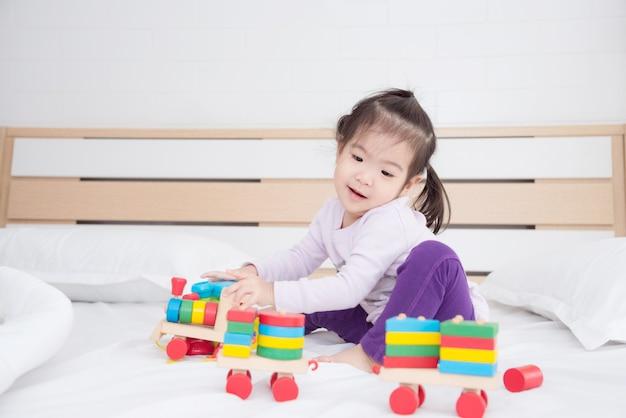 Weinig aziatische meisjeszitting op bed en het spelen van speelgoed thuis