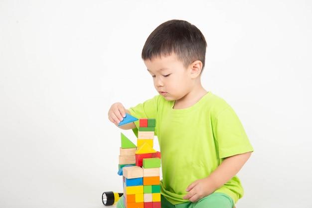 Weinig aziatische peuterjongen die houtsneden spelen draagt helmingenieur