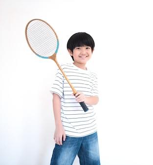 Weinig aziatische schooljongen met racket die op witte muur wordt geïsoleerd