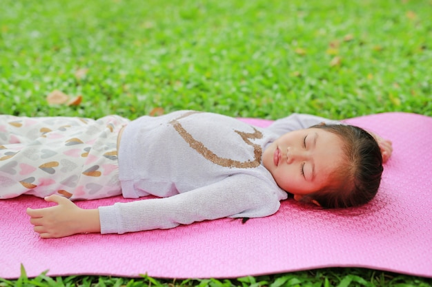 Weinig aziatische slaap van het kindmeisje op roze matras in groen grasgazon bij de tuin van het de zomerpark.