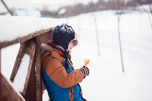 Weinig baby die en zoete jonge haan in de winterdag spelen eten. kinderen spelen in besneeuwde bossen.