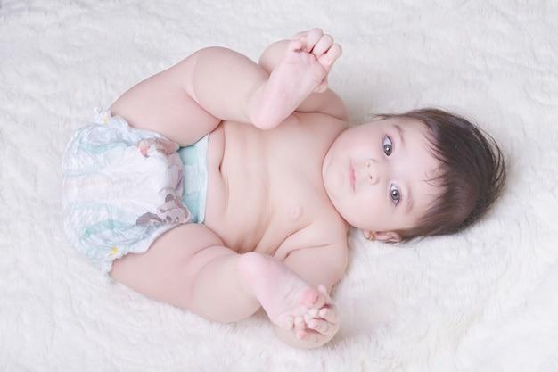 Weinig baby die met zijn voeten op witte pluizige deken speelt.