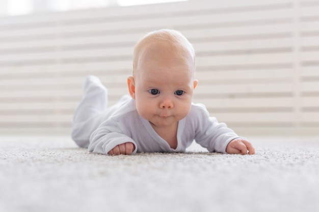 Weinig baby die op vloer thuis kruipt