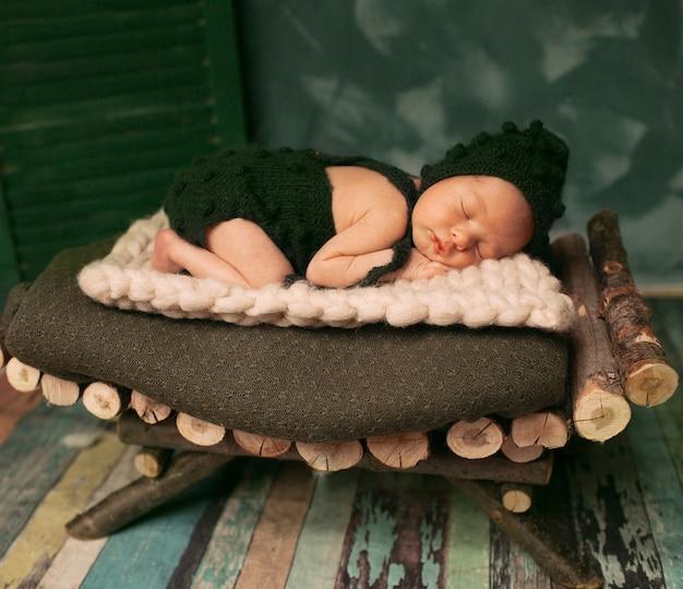 Weinig baby in donkergroene wollen kleren slaapt op een houten bed