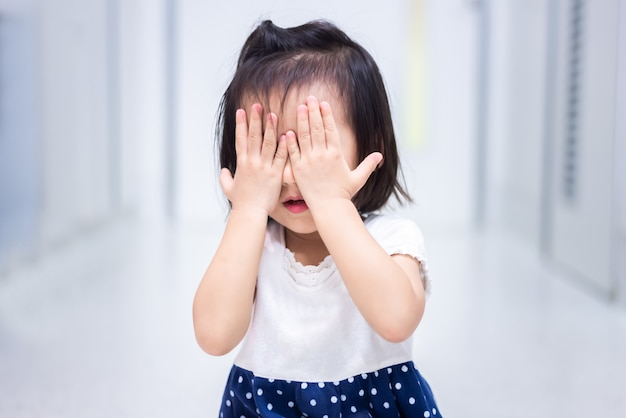 Weinig baby kind zittend op de grond huilen en bedek haar gezicht met haar hand