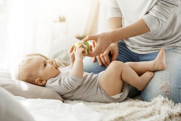 Weinig babyjongen die gelukkige kinderjaren met jonge moeder doorbrengen. kind dat een mooi stuk speelgoed van tedere mammahanden probeert te nemen. familie concept.
