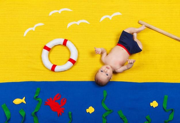 Weinig babyjongen die op blauwe achtergrond ligt. grappig kind dat het zwemmen imiteert en in het water springt