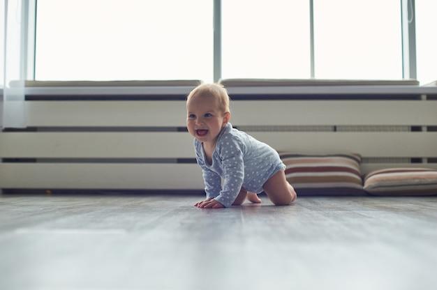 Weinig babyjongen die op vloer thuis kruipt