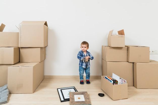 Weinig babyjongen die zich tussen de bewegende kartondozen bij nieuw huis bevindt