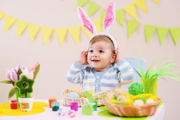 Weinig babyjongen in konijnoren glimlachen die bij lijst met pasen-decor zitten