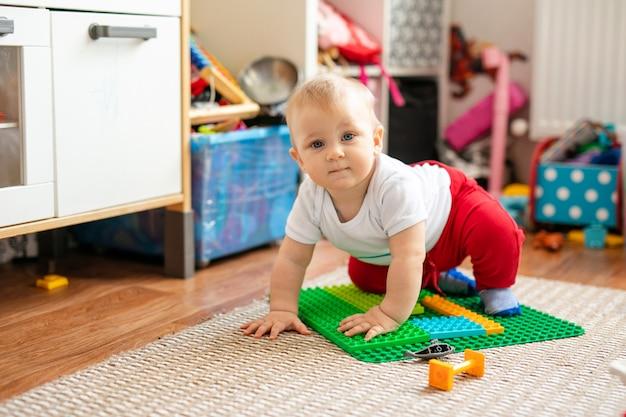 Weinig babyjongen in witte t-shirt met speelgoed op de vloer thuis