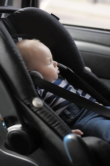Weinig babyjongen met dichte ogen in autozetel