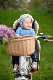 Weinig babyjongen met een kapzitting als fietsvoorzitter