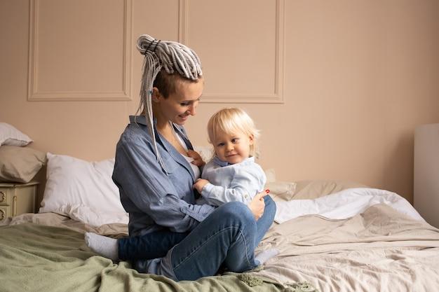 Weinig babyjongen op bed met zijn moeder die pret heeft