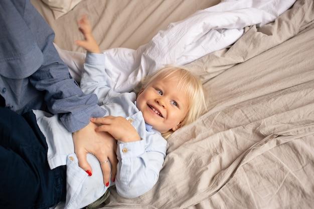 Weinig babyjongen op bed met zijn ouders die pret hebben