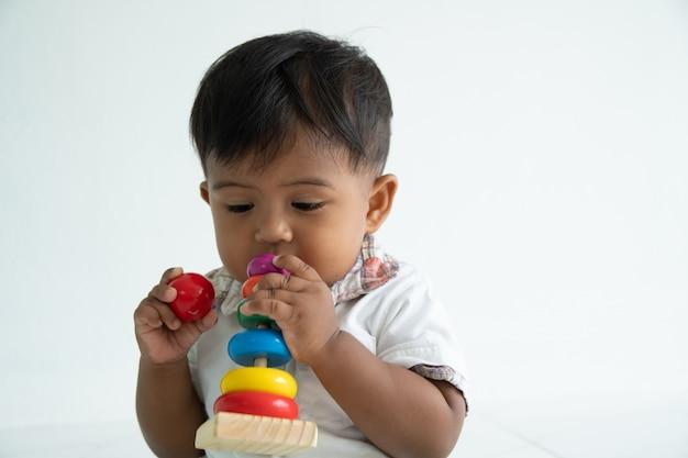 Weinig babyjongen speelt houten stuk speelgoed bij ruimte