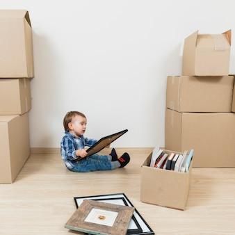 Weinig babyjongen zit tussen de bewegende kartonnen dozen kijken naar foto frame bij nieuw huis
