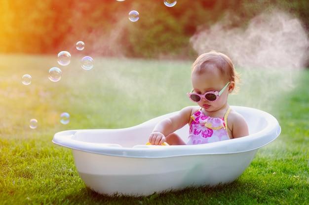 Weinig babymeisje baadt in bad op weide