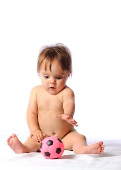 Weinig babymeisje dat met kleine roze voetbalbal speelt