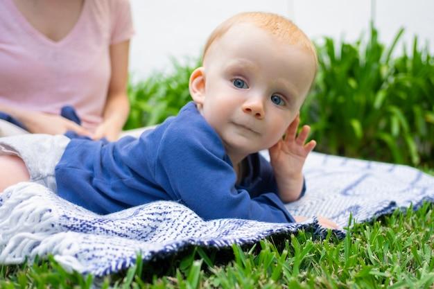 Weinig babymeisje dat op plaid ligt, hand dichtbij gezicht houdt en weg kijkt. closeup portret in tuin. jonge moederzitting. familie zomertijd, zonnige dagen en frisse lucht concept