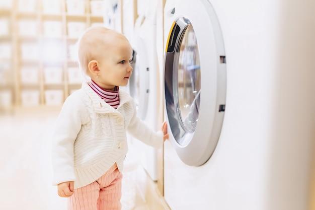 Weinig babymeisje die een wasmachine bekijken