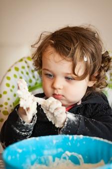Weinig babymeisje die met deeg spelen