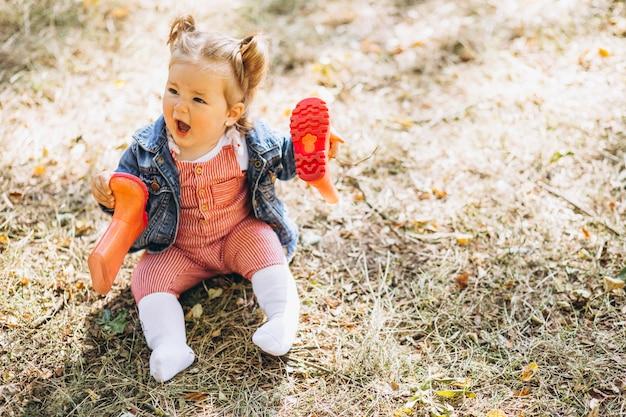 Weinig babymeisje die met regenlaarzen in park zitten