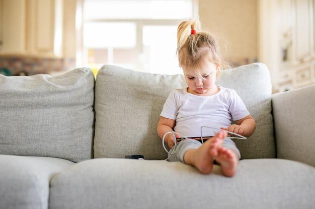 Weinig babymeisje die met smartphone thuis spelen.