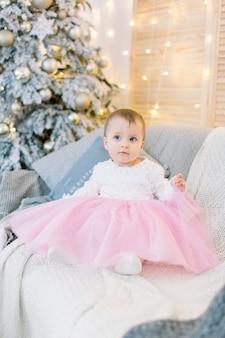 Weinig babymeisje en kerstmis. leuk meisje, zittend op de bank, op de achtergrond van de kerstboom.