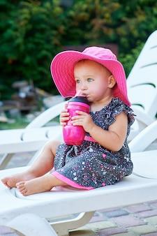 Weinig babymeisje in de herfstpark drinkt van roze plastic fles