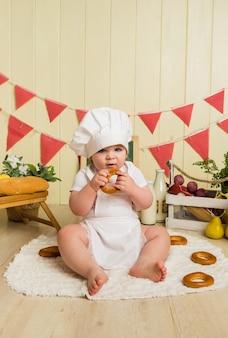 Weinig babymeisje in een witte pet en een schort zit en eet een ongezuurd broodje