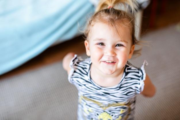 Weinig babymeisje in witte t-shirt met speelgoed op de vloer thuis