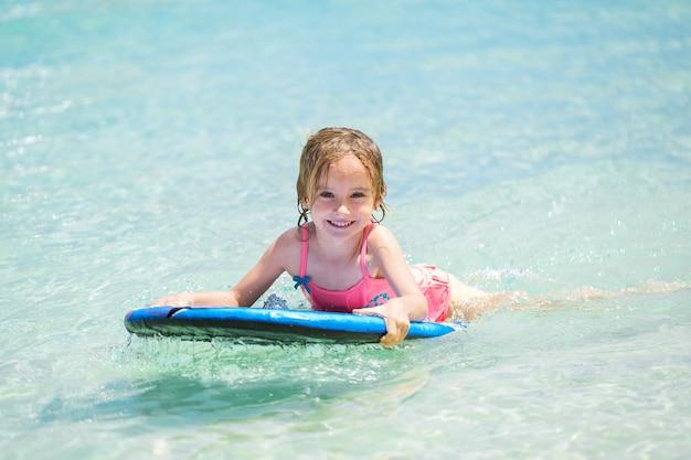 Weinig babymeisje - jonge surfer met bodyboard heeft een plezier op kleine oceaangolven. actieve gezinslevensstijl