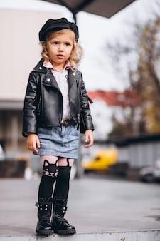 Weinig babymeisje kleedde zich in modieuze uitrusting in park