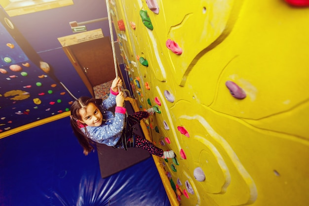 Weinig babymeisje met grappige hoort stijl beklimmende verticale muur en man die haar vastmaken van onderaan