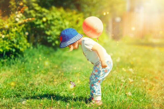Weinig babymeisje op de magische weide met ballon
