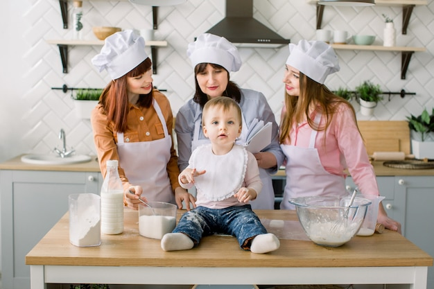 Weinig babymeisje zit op de houten lijst bij keuken terwijl haar moeder, tante en grootmoeder het boek met recepten op de achtergrond lezen. gelukkige vrouwen in witte schorten samen bakken