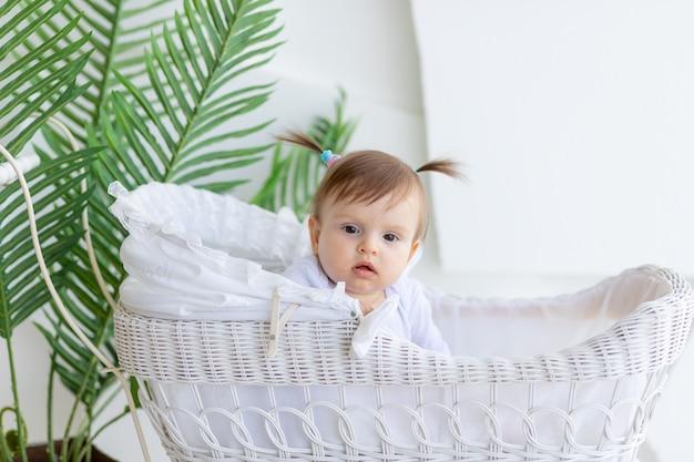 Weinig babymeisje zit thuis in een witte wandelwagen met een verbaasde blik