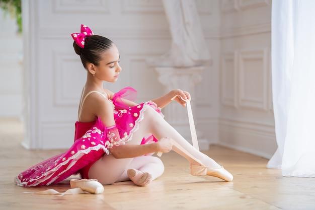 Weinig ballerina in een helderroze tutu zit op de vloer in helder