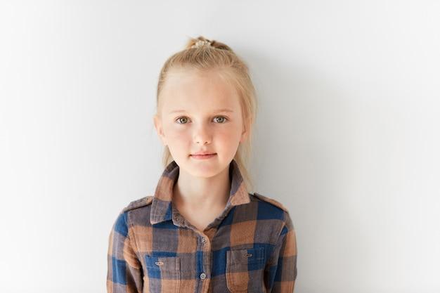 Weinig blond meisje dat gestreept overhemd draagt