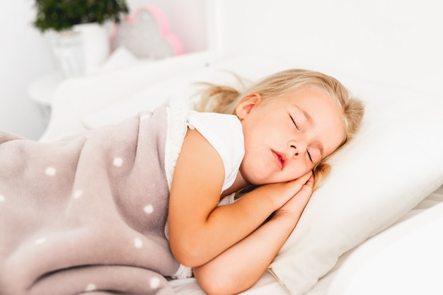 Weinig blond meisje slaapt op wit bed met haar handen onder haar wang.
