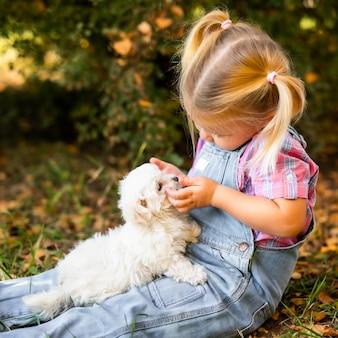 Weinig blond peutermeisje dat met twee vlechten met aardig wit puppy speelt