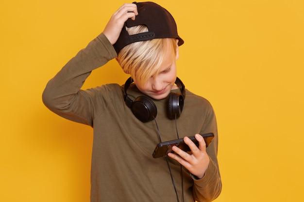 Weinig blonde jongen die in groene sweater en blackcap draagt