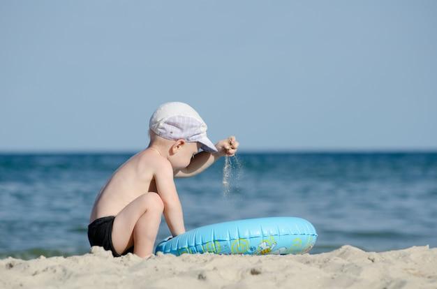 Weinig blonde jongen die met zand op de kust speelt