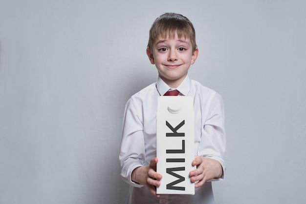 Weinig blonde jongen houdt en toont een groot wit pakketmelkpakket. wit overhemd en rode stropdas. licht