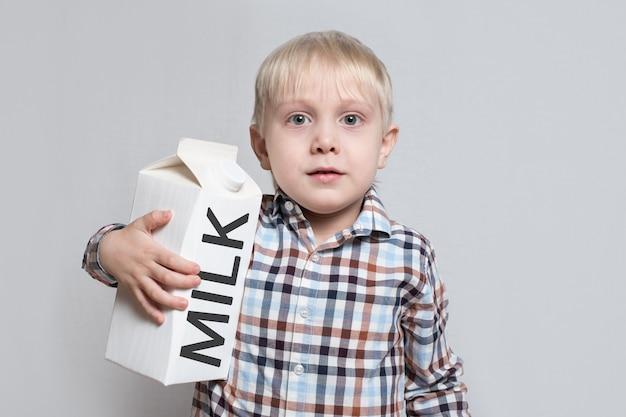Weinig blonde jongen knuffelt een groot wit kartonmelkpakket.